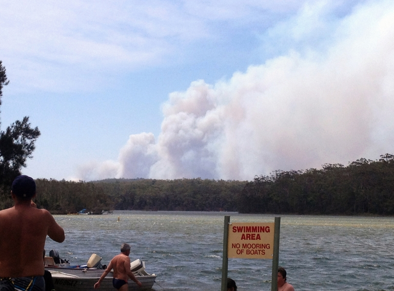 <p>This picture taken from Lake Conjola shows bathers looking on as smoke billows from a bushfire (back) at Deans Gap in New South Wales on January 8, 2013.</p>