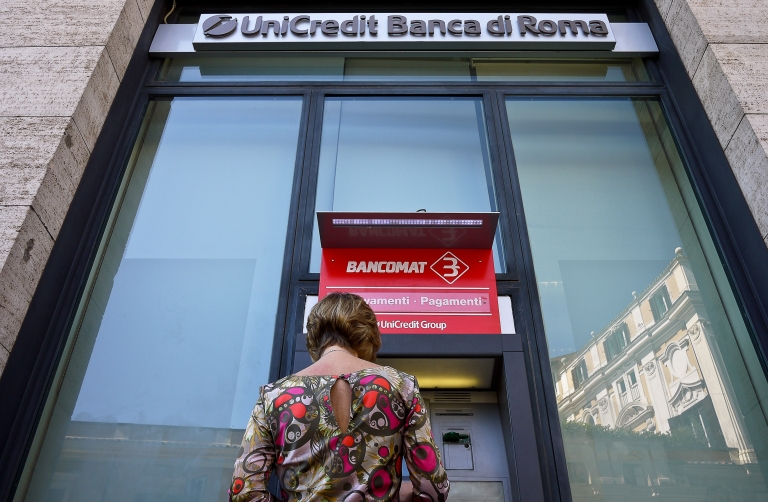 <p>A customer at an automatic teller machine at a Unicredit Bank branch in Rome on September 2011. The Fitch ratings agency has joined Moody's and Standard &amp; Poor's in downgrading Italy's credit rating.</p>