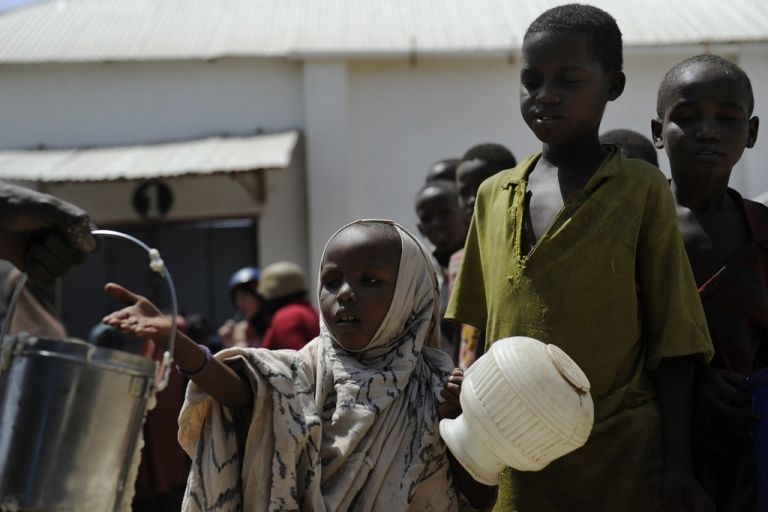 <p>Displaced Somali children wait in line for food aid rations on January 19, 2012 at a UN distribution center in the capital Mogadishu. A new report by Transparency International warns that direct deliveries of food are prone to corruption.</p>