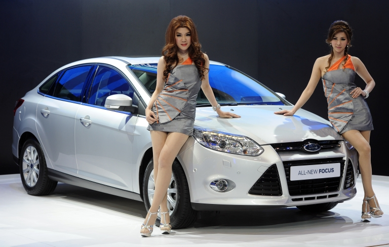 <p>Thai models pose next to a Ford Focus on display at the 33rd Bangkok International Motor Show in Thailand on Mar. 27, 2012.</p>