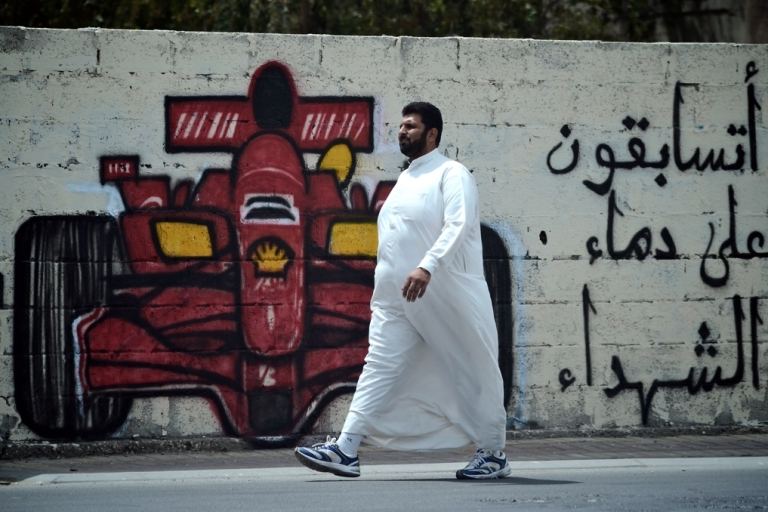 <p>A man in Bahrain walks past graffiti calling for the cancellation of the Formula One Grand Prix in Bahrain later this month. The sign reads,