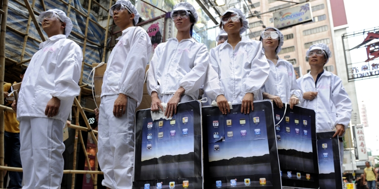 <p>Participants dressed up to represent Foxconn workers take part in a protest against the Taiwanese technology giant, which manufactures Apple products in mainland China, outside an Apple retail outlet in Hong Kong on May 7, 2011. At least 13 Foxconn employees died in apparent suicides last year, which rights activists blamed on tough working conditions in a case that highlighted the challenges faced by millions of Chinese factory workers.</p>