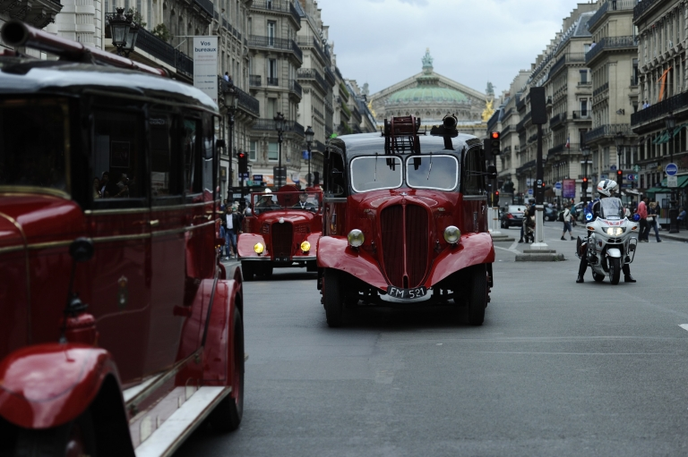 <p>Firemen from the Paris brigade (Sapeurs-Pompiers de Paris) drive an old fire engine with the city's Opera Garnier in the background.</p>