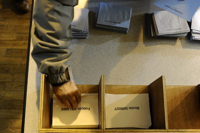 <p>A French voter in the central town of Tulle takes ballots papers to vote in the second round of the 2012 French presidential election on May 6.</p>