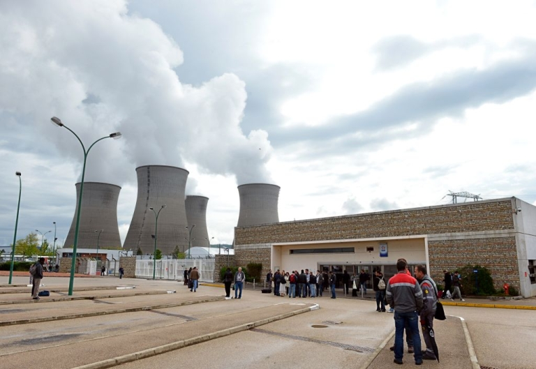 <p>Employees of the Bugey nuclear power plant wait outside the plant on May 2, 2012 after a Greenpeace activist flew into the grounds of the plant using a motorized paraglider.</p>