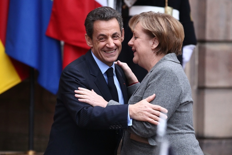 <p>French President Nicolas Sarkozy and German Chancellor Angela Merkel prior to a meeting with Italian Prime Minister Mario Monti on November 24, 2011 in Strasbourg, France. French pundits say Sarkozy caved to a Merkel plan that won't work.</p>