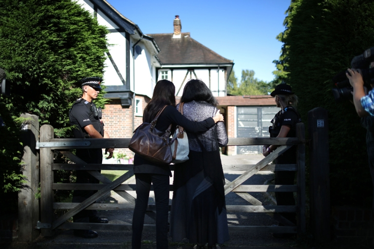 <p>Two women, who identified themselves as family friends, hold each other as they stand at the front gate of the house of the al-Hilli family on September 7, 2012 in Claygate, England.</p>
