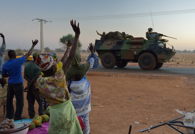 <p>Malian people wave to French soldiers heading north from Bamako under the 'Serval' operation, on January 15, 2013. France is using air and ground power in a joint offensive with Malian soldiers launched on January 11 against hardline Islamist groups controlling northern Mali.</p>