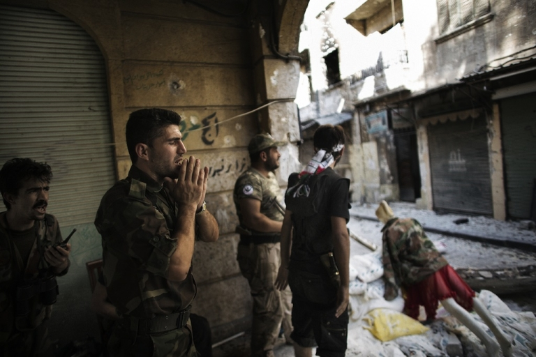 <p>A Free Syria Army fighter yells 'Allahu Akbar' (God is Great) as he mans a position with his comrades only 50 meters away from a Syrian army post in the Old City of Aleppo September 16, 2012. More than 27,000 people have been killed since the uprising against President Bashar al-Assad's rule erupted in March last year, the Britain-based Observatory estimates. The United Nations puts the toll at 20,000.</p>