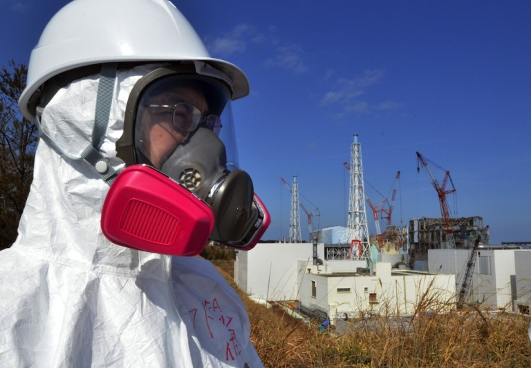 <p>This file photo taken on February 28, 2012 shows a journalist looking at the stricken Fukushima Daiichi nuclear power plant in the town of Okuma, Fukushima prefecture.</p>