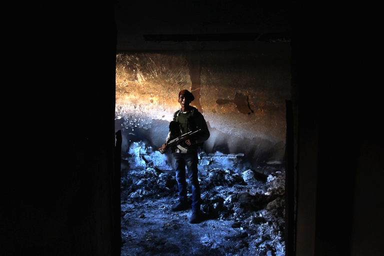 <p>A rebel militiaman stands in the ashes of an alleged torture chamber of the former Libyan Internal Security force in Benghazi, Libya. Feb. 28, 2011. The notorious building was mostly burned in the uprising that drove loyalists to President Muammar Gaddafi out of Bengazi the week before.</p>