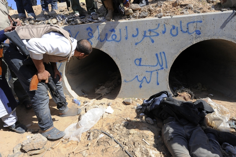 <p>A Libyan National Transitional Council (NTC) fighter looks through a large concrete pipe where ousted Libyan leader Muammar Gaddafi was allegedly captured, with a dead loyalist gunmen in the foreground, in the coastal Libyan city of Sirte. Oct. 20, 2011.</p>