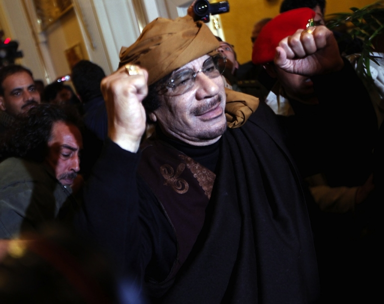 <p>Libyan strongman Muammar Gaddafi gestures as he arrives at the Rixos hotel in the capital Tripoli on March 8, 2011.</p>
