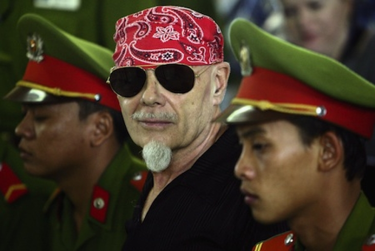 <p>Disgraced glam rocker Gary Glitter is flanked by Vietnamese police as his guilty verdict for sex crimes is read at a courthouse in Ba Via, Vietnam, in 2006.</p>