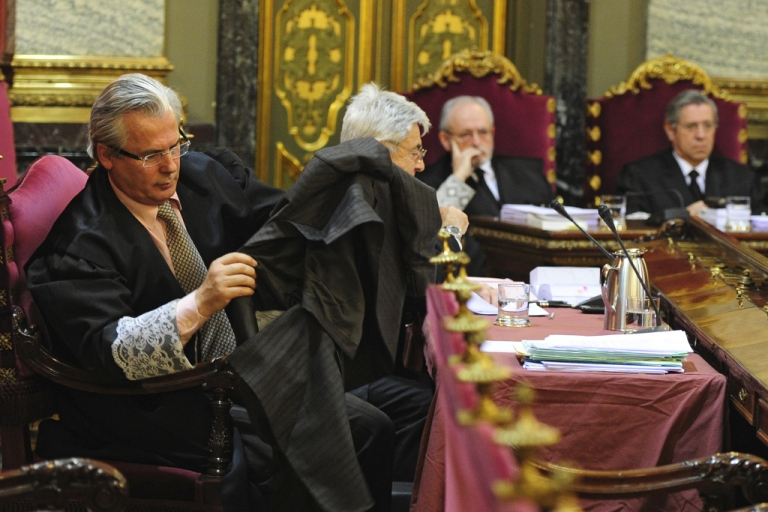 <p>Spanish prosecuting judge Baltasar Garzon puts on his robes at the start of his trial today in Madrid</p>