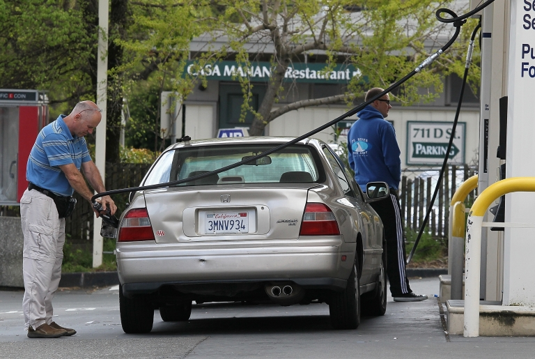 <p>Customers pump gas into their cars at an Arco gas station in San Rafael, Calif.</p>