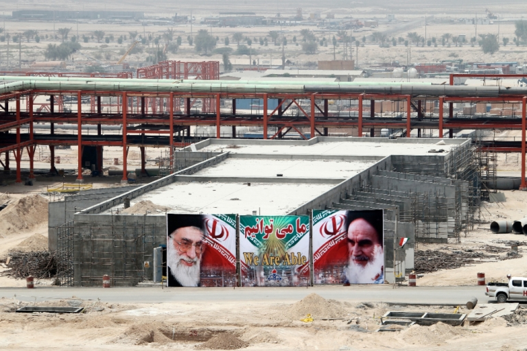 <p>A huge banner bearing portraits of Iran's supreme leader Ayatollah Ali Khamenei (L) and his predecessor, the founder of the Islamic Republic, Ayatollah Ruhollah Khomeini (R), is seen on a building being constructed at phase 15 and 16 of South Pars gas field development in the southern Iranian port town of Asaluyeh on July 19, 2010.</p>