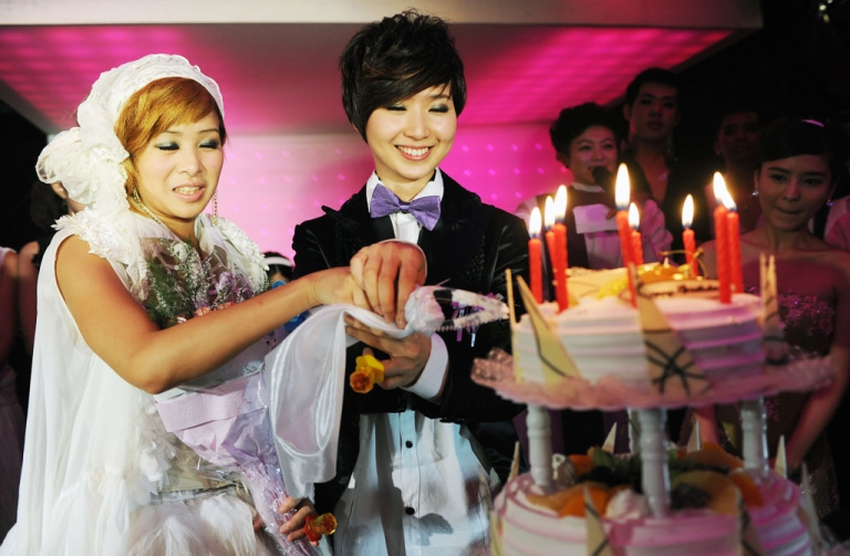 <p>A same sex couple cut a cake during a mass 'wedding' party event in Taipei on August 21, 2011.</p>