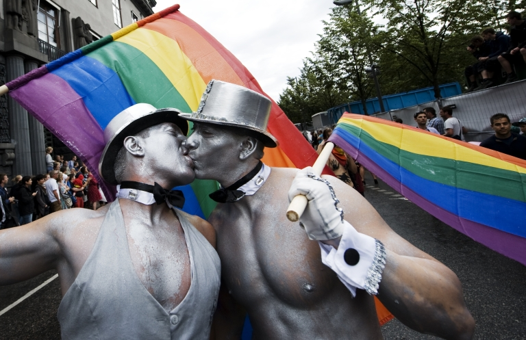 <p>Men kiss during the Stockholm Pride parade in central Stockholm on Aug. 6, 2011.</p>
