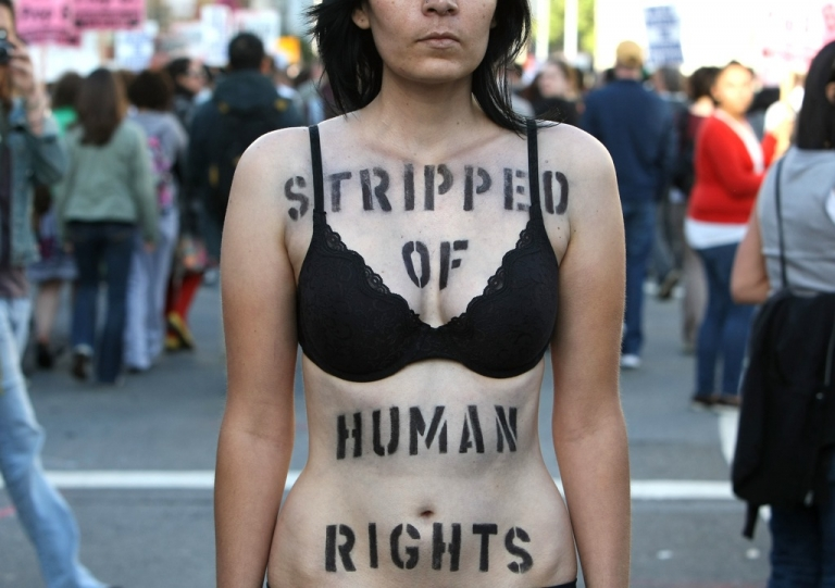 <p>Helaine Gawlica stands with a spray painted message on her body during a march and rally following the California Supreme Court's ruling to uphold Proposition 8 May 26, 2009 in San Francisco, California. Civil rights for the LGBT community has largely fell to the states with anti-discrimination and legal rights for gays and lesbians largely varying statewide.</p>