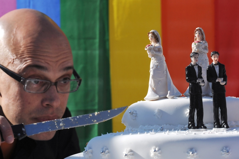 <p>A gay activist prepares to cut a wedding cake in front of the Portuguese parliament in Lisbon on January 8, 2010, after the approval at first reading a bill to legalize same sex marriages less than 30 years after the country revoked its ban on homosexuality. Lawmakers rejected proposals to allow gay couples to adopt, but otherwise the bill passed with little public controversy in what has traditionally been one of Europe's most socially conservative countries.</p>