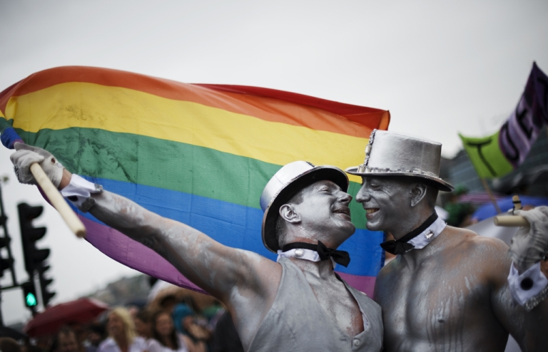 <p>Men kiss during a gay pride parade. Dr. Robert Spitzer, the founder of the