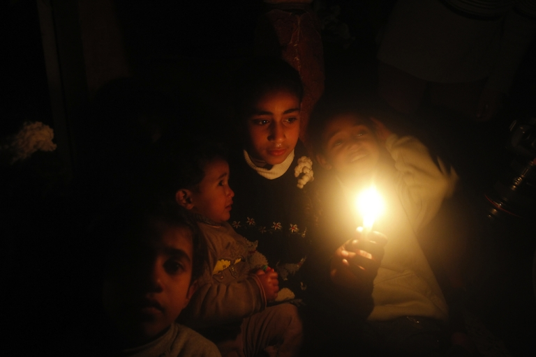 <p>Palestinian children sit at their home during a power cut at the Shati refugee camp in Gaza City earlier this month.</p>