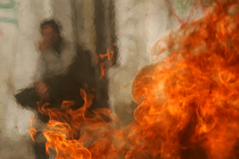 <p>A file photo from 2006 of a man standing next to a burning car in the Gaza Strip. At the time, violence flared between Fatah and Hamas. Recent efforts at reconciliation between the two rival factions are faltering.</p>