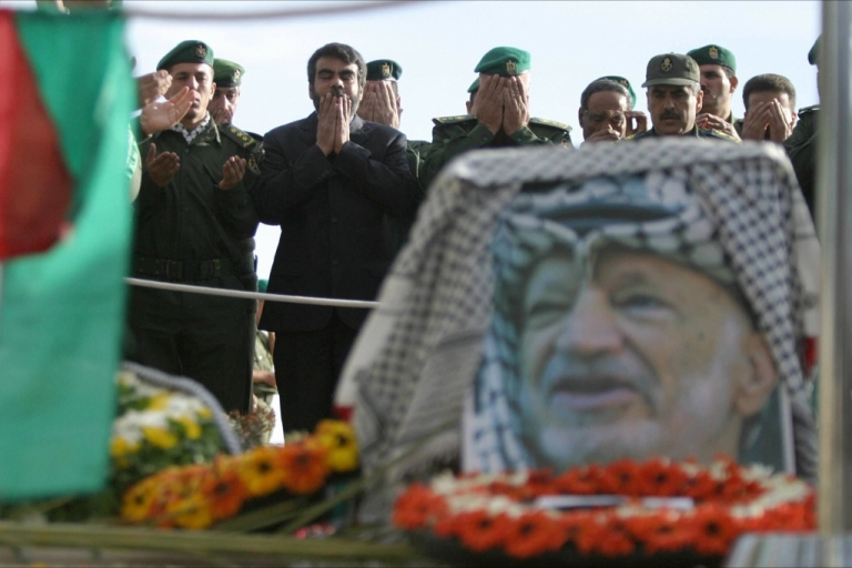 <p>Palestinian officers pray around the grave of late Palestinian leader Yasser Arafat inside his Muqataa compound in the West Bank town of Ramallah 13 November 2004.</p>