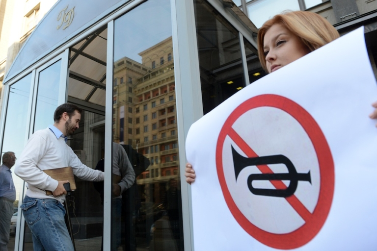 <p>A pro-Kremlin demonstrator attends a rally against Gennady Gudkov, deputy head of the Just Russia party, in front of Russia's lower house of parliament, the State Duma, in Moscow, on Sept. 14, 2012. The 'No horns' road sign is a reference to Gudkov's family name, which means (Horn).</p>