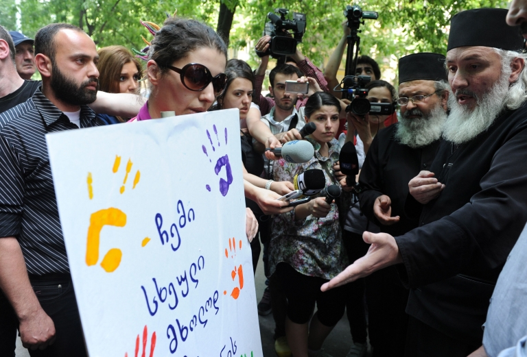 <p>Orthodox priests (R) argue with gay rights activists (L) as they rally in the Georgian capital Tbilisi on May 17, 2012.</p>