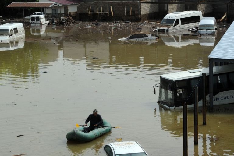 <p>A man rows a dinghy in the flooded street of Tbilisi's district Ortachala after heavy overnight rain on May 13, 2012</p>