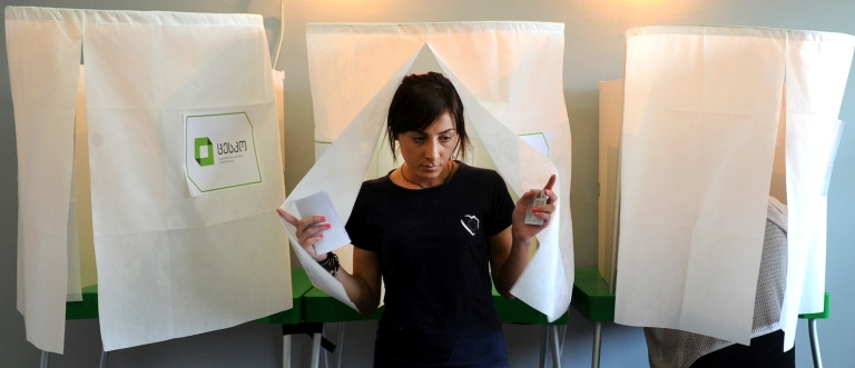 <p>A woman leaves a voting booth at a polling station in Tbilisi, on October 1, 2012.</p>