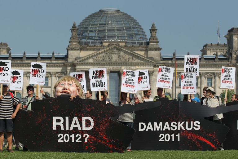 <p>Activists hold signs that read 'Stop Tank Exports To Saudi Arabia!' and 'No Tanks To Riad!' as they stand behind effigies of tanks while protesting near the Reichstag on July 6, 2011 in Berlin, Germany.</p>