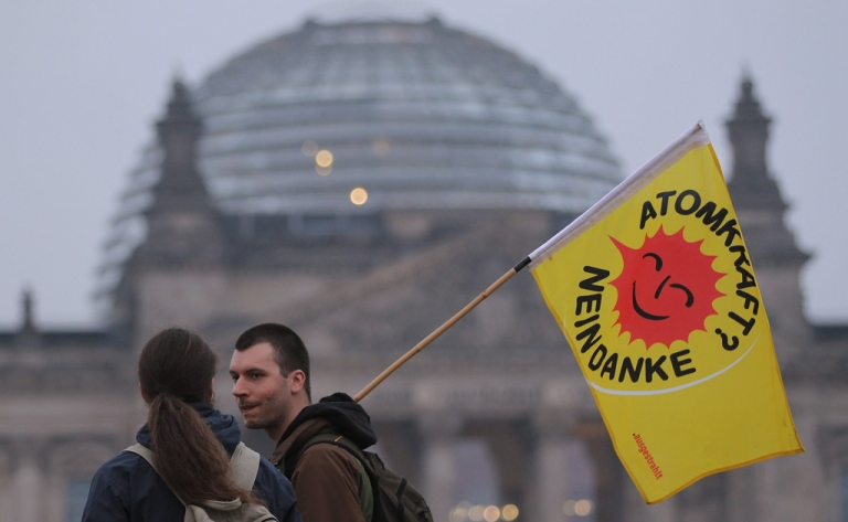 <p>Anti-nuclear activists walk past the Reichstag following a demonstration on March 14, 2011 in Berlin, Germany.</p>