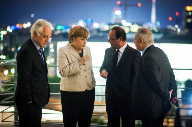 <p>In Berlin, German Chancellor Angela Merkel speaks with new French President Francois Hollande next to two translators before a working dinner at the Chancellery hours after Hollande's inauguration in Paris on May 15, 2012.</p>