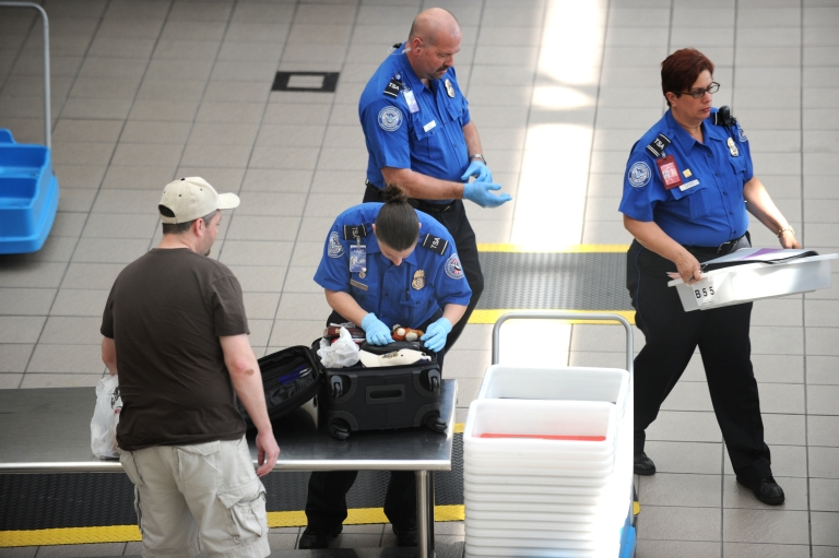 <p>Transportation Security Administration agents check passengers' bags on May 2, 2011, at Orlando International Airport in Orlando, Fla.</p>