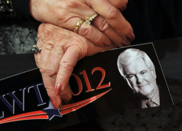 <p>A supporter of Republican presidential hopeful Newt Gingrich holds a bumper sticker at a rally in Golden, Colorado.</p>