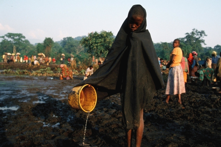 <p>A Rwandan gathering polluted water at the largest refugee camp at Kitali, eastern Congo. Thousands of Hutus died of a cholera epidemic after escaping Rwanda where they were responsible for the killing of almost one million Tutsis.</p>