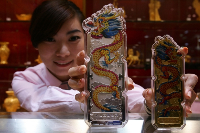 <p>An employee shows off silver and gold bullion bars engraved with dragons at a gold shop in Beijing on September 15, 2011.</p>