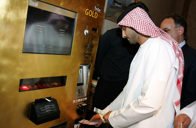 <p>An Emirati man tries the 'Gold to Go' vending machine at the Emirates Palace Hotel in Abu Dhabi in May, 2010. The well-heeled in the Gulf can now grab 'gold to go' from a hotel lobby in the United Arab Emirates, when the need for a quick ingot strikes. The machine, itself covered in 24-carat gold, dispenses one, five and 10 gram bars as well as one ounce bars of gold.</p>