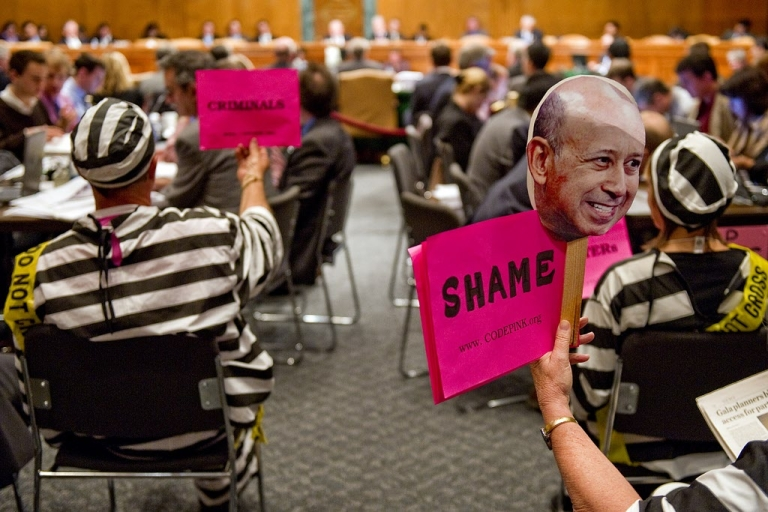 <p>Code Pink demonstrators hold placards during a Senate hearing on April 27, 2010. Goldman Sachs denied reaping vast profits from the collapse of the US housing market as its top executive and a star trader faced hostile questions in Congress over the 2008 financial meltdown.</p>
