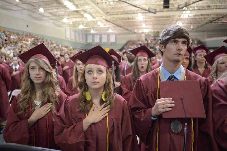<p>Students listen to then national anthem prior to US President Barack Obama's delivering of the commencement address on May 21, 2012 at Missouri Southern State University in Joplin, Missouri.</p>