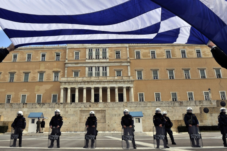 <p>Holding a Greek flag bus employees protest in front of the Greek Parliament in Athens on Feb. 1, 2011.</p>