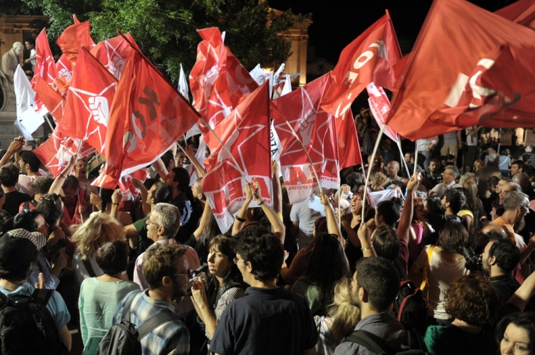 <p>Radical left Syriza party supporters listen to their leader making a speech on June 17, 2012, outside the University of Athens.</p>