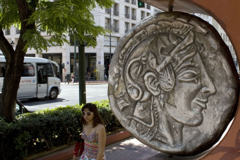 <p>A woman pass by replica of an ancient Drachma coin in Athens. The Greek electorate are due to go to the polls in a re-run of the general election on June 17, 2012 after no combination of political parties were able to form a coalition government.</p>