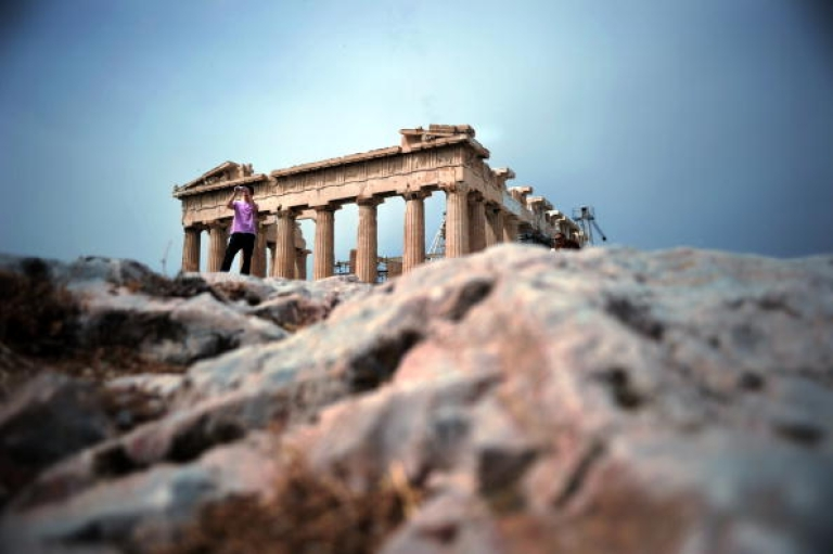 <p>A tourist takes pictures at the Acropolis archeological site in Athens on May 8, 2010.</p>