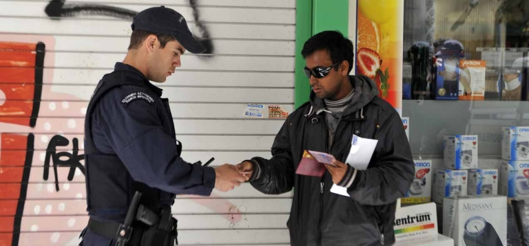 <p>Police check an immigrant's papers in central Athens' Omonia square area, March 29, 2012.</p>