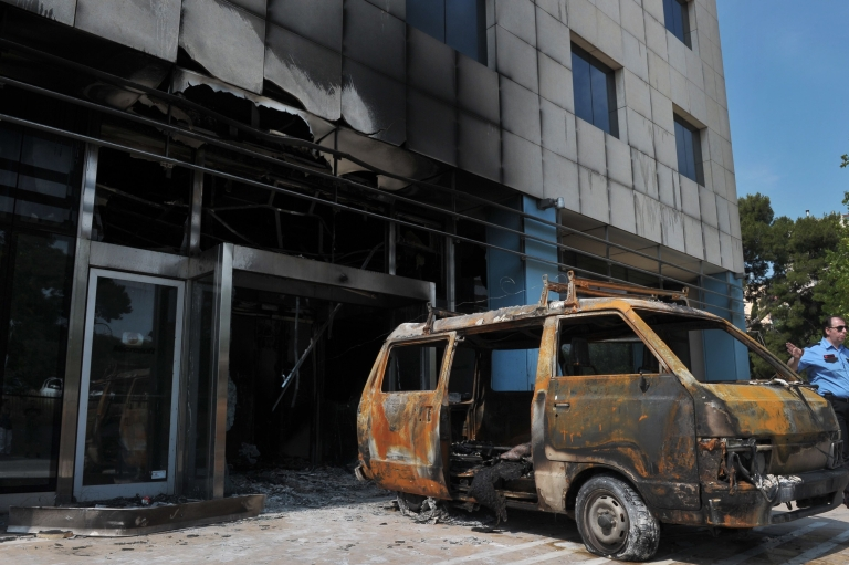 <p>A security officer stands by the mini-van used by attackers at entrance to the Microsoft office in an Athens northern suburb on June 27, 2012.</p>