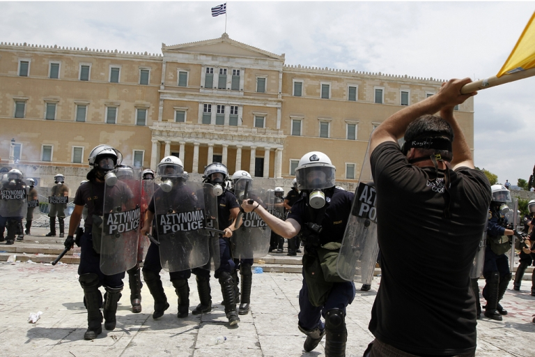 <p>Protesters clash with riot police in front of the Greek Parliament on June 29, 2011 in Athens, as lawmakers voted on a massive austerity package demanded by international creditors.</p>